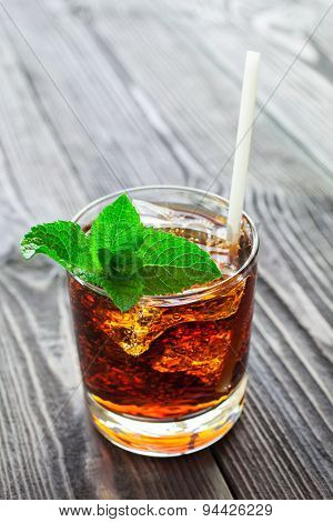 Glass Of Cola With Ice And Fresh Mint On Wooden Table.