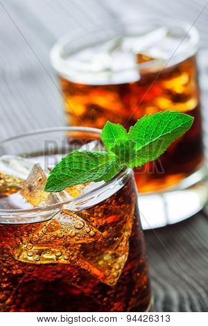 Two Glasses Of Cola With Ice And Fresh Mint On Wooden Table.