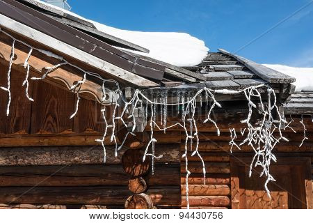 Chalet Close-up: Gutter With Ice And Turned Off Christmas Lights
