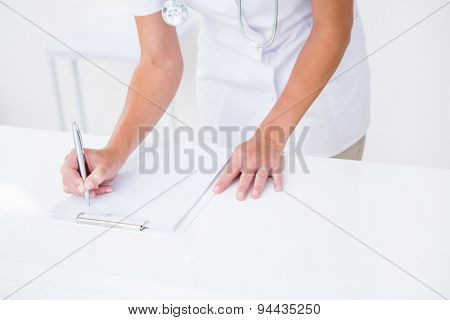 Doctor writing on clipboard at her desk in medical office
