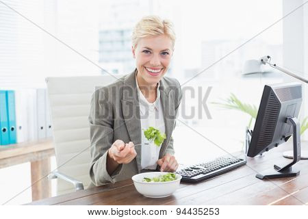 Businesswoman eating salad on her desk in her office