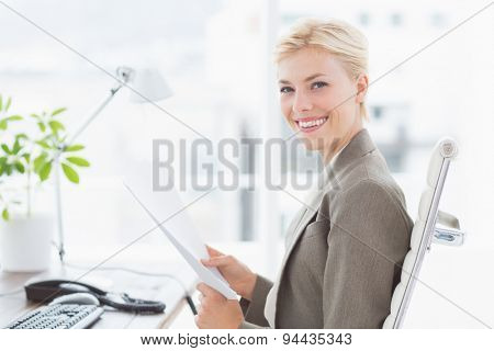 Smiling businesswoman looking at camera in her office