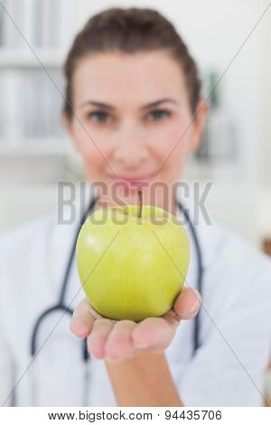 Smiling doctor showing apple in medical office