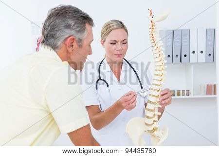 Doctor showing her patient a spine model in medical office