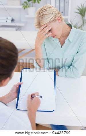 Patient with head ache ache speaking with her doctor in medical office
