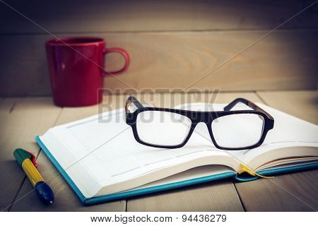 Diary and coffee cup, with reading glasses. Toned image, focus on reading glasses.