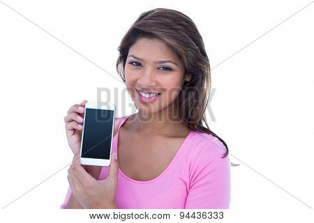 Pretty brunette smiling at camera and holding a smartphone on white background