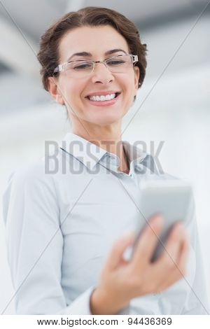 Smiling businesswoman using her smartphone in an office