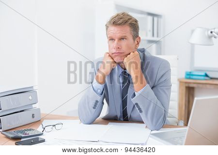 Worried businessman sitting at work in his office