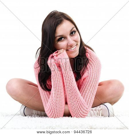 Smiling fitness young woman sitting isolated against white background