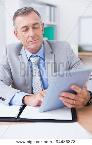 Businessman looking at work schedule in his office