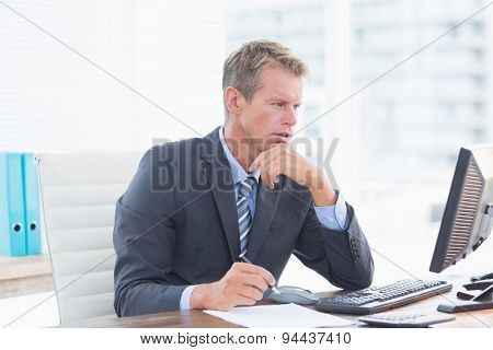 Serious businessman on his pc in his office