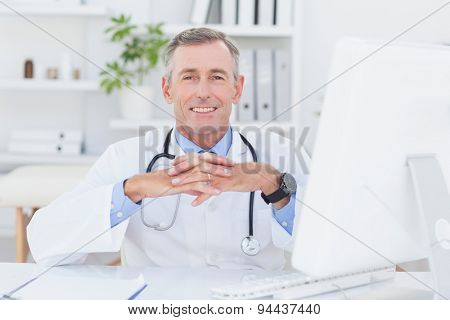 Smiling doctor looking at camera with hands crossed in medical office