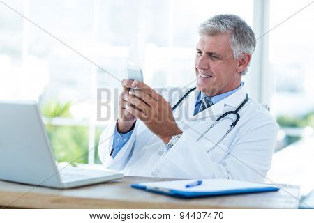 Smiling doctor sitting at his desk and texting in medical office