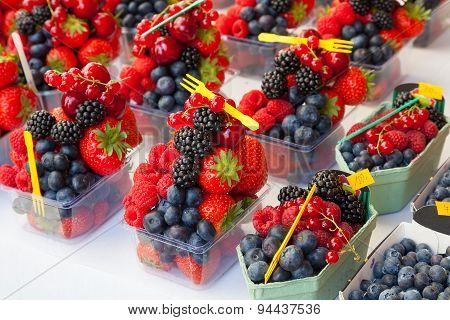 Colorful Arrangement Of Fresh Fruit Berries Ready To Eat On A Market Stall.