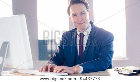 Smiling businessman typing on laptop and looking at camera in office