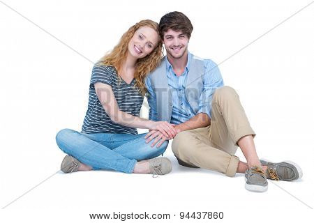 Happy couple sitting on the floor on white background