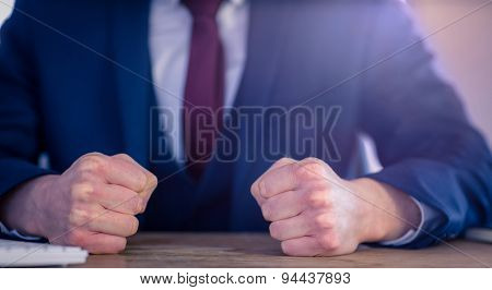 Angry businessman with closed fists in his office
