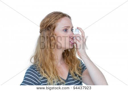 Pretty blonde using an asthma inhaler on white bakcground