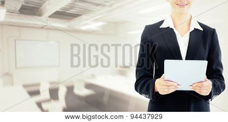 Businesswoman holding tablet against classroom