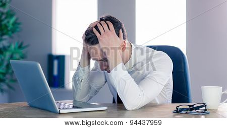 Upset businessman with head in hands in his office