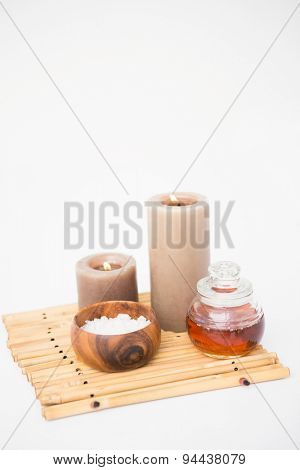 Perfumed candles and beauty products on a bamboo mat