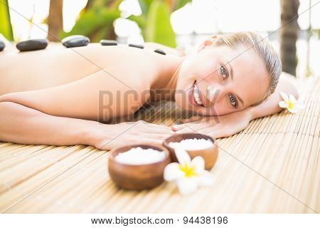 Portrait of a beautiful young woman receiving stone massage at spa center