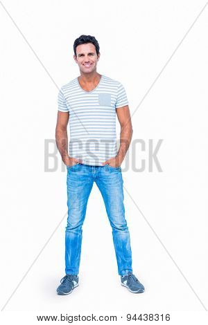 Happy man smiling at camera with hands in pocket on white background