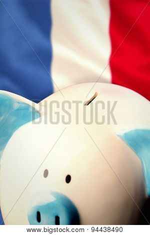 Piggy bank against digitally generated france national flag