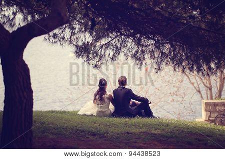 Bride And Groom Sitting At Lake