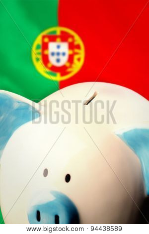 Piggy bank against digitally generated portugese national flag