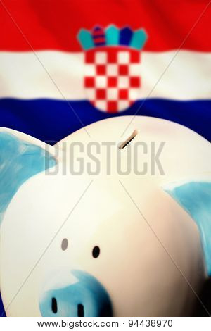 Piggy bank against digitally generated croatia national flag
