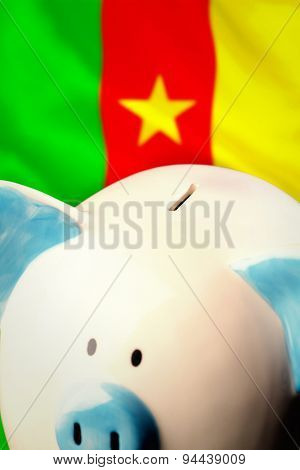 Piggy bank against digitally generated cameroon national flag