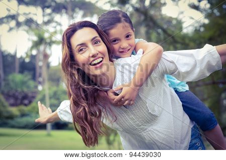 Happy little girl getting a piggy back from mother in the park on a sunny day