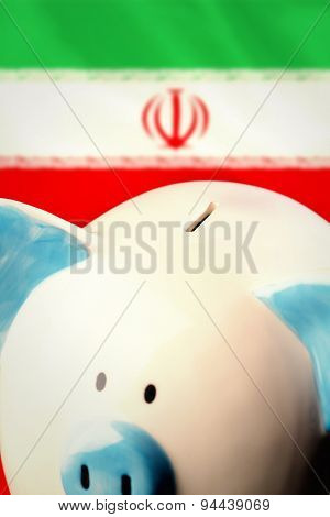 Piggy bank against digitally generated iran national flag