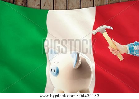 hand holding hammer against digitally generated italian national flag