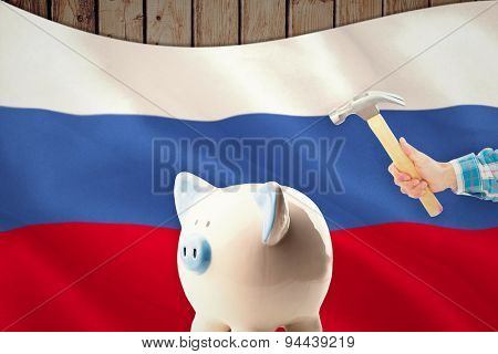 hand holding hammer against digitally generated russian national flag
