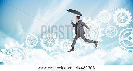 Businessman jumping holding an umbrella against blue sky