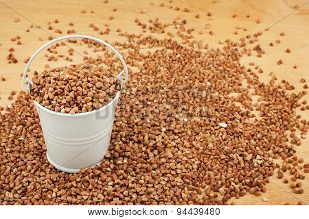 White Bucket Of Buckwheat On The Wooden Floor