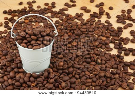 White Bucket With Coffee Beans  On The Wooden Floor