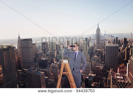 Businessman looking on a ladder against new york skyline