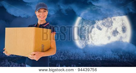 Happy delivery woman holding cardboard box against large moon over city