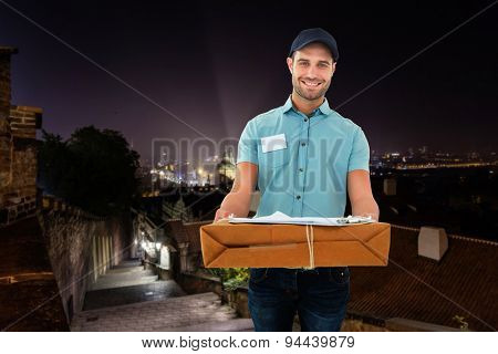 Handsome courier man with parcel against cityscape by night