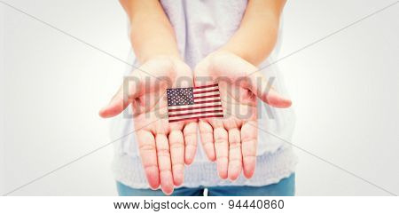 Casual young woman holding hands out against usa national flag