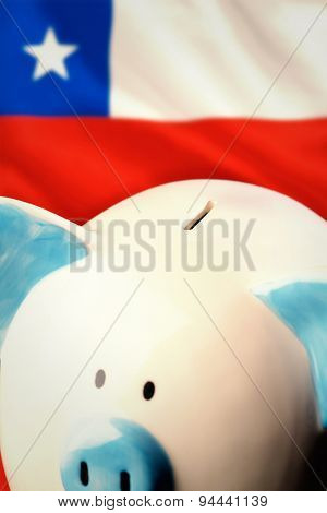 Piggy bank against digitally generated chile national flag