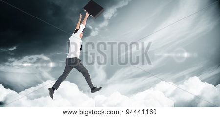 Businessman leaping with his briefcase against blue sky