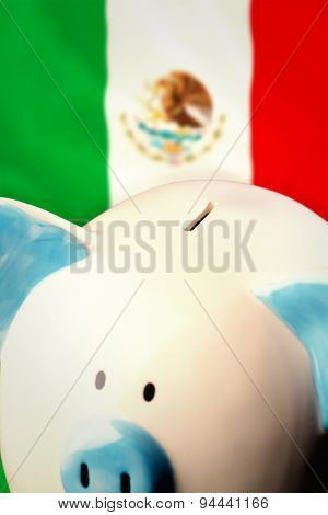 Piggy bank against digitally generated mexican national flag