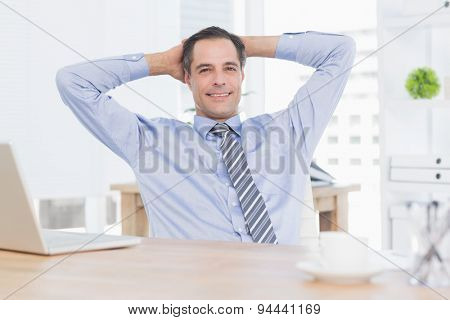 Smiling businessman relaxing on his office