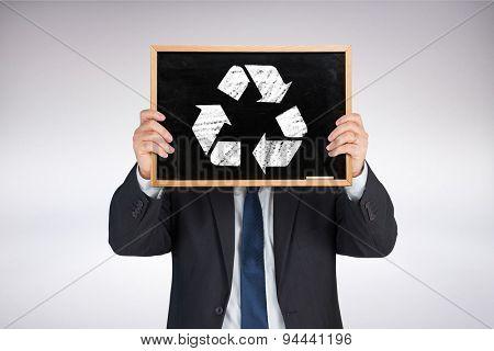 Businessman showing board against grey background