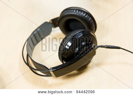 technology, electronics and audio equipment concept - close up of headphones at recording studio or radio station